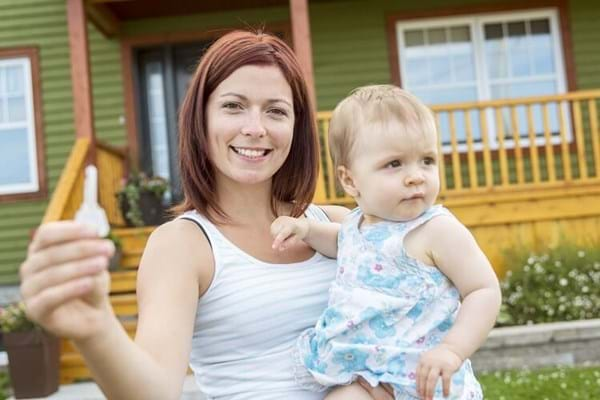 Woman holding small child standing in front of house with key