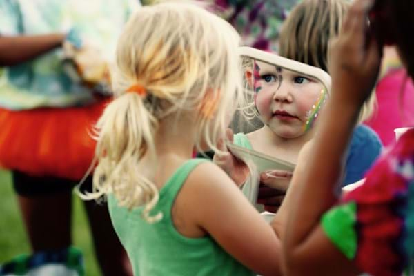 Little girl looking at facepaint in the mirror