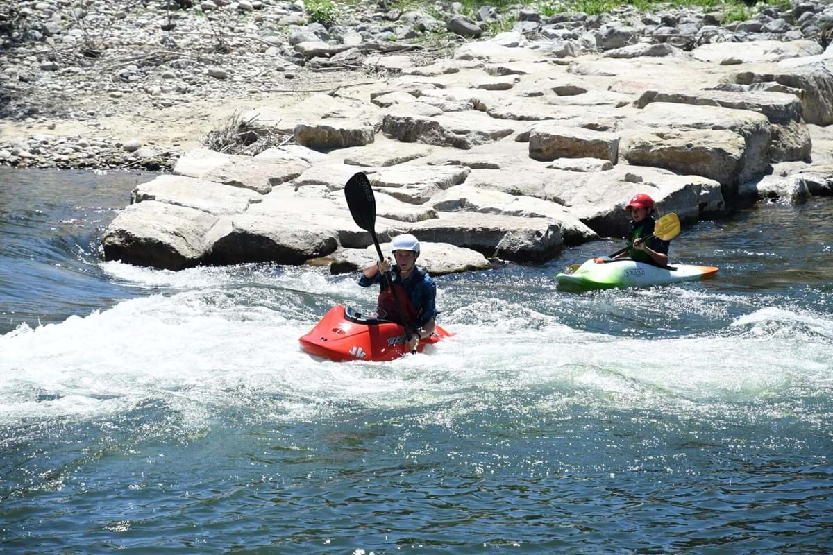 Two individuals in kayaks on rapid at Boise Whitewater Park