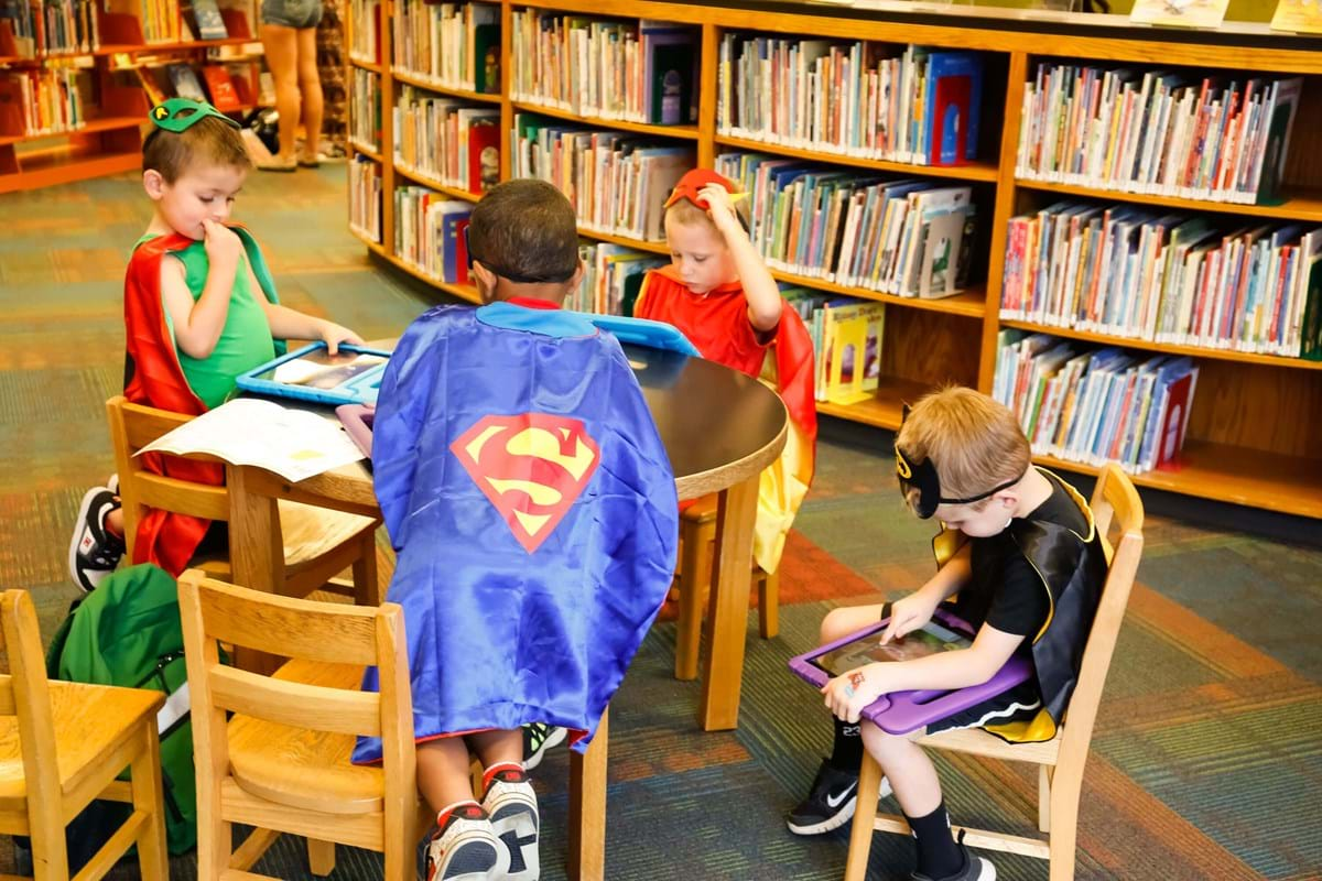 Kids sitting around table at library wearing superhero capes