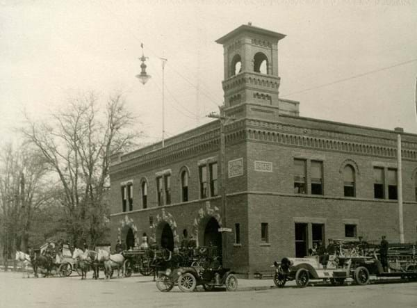 Photo from around 1912. 2 story brick building with bell tower featuring horse-pulled fire wagons.