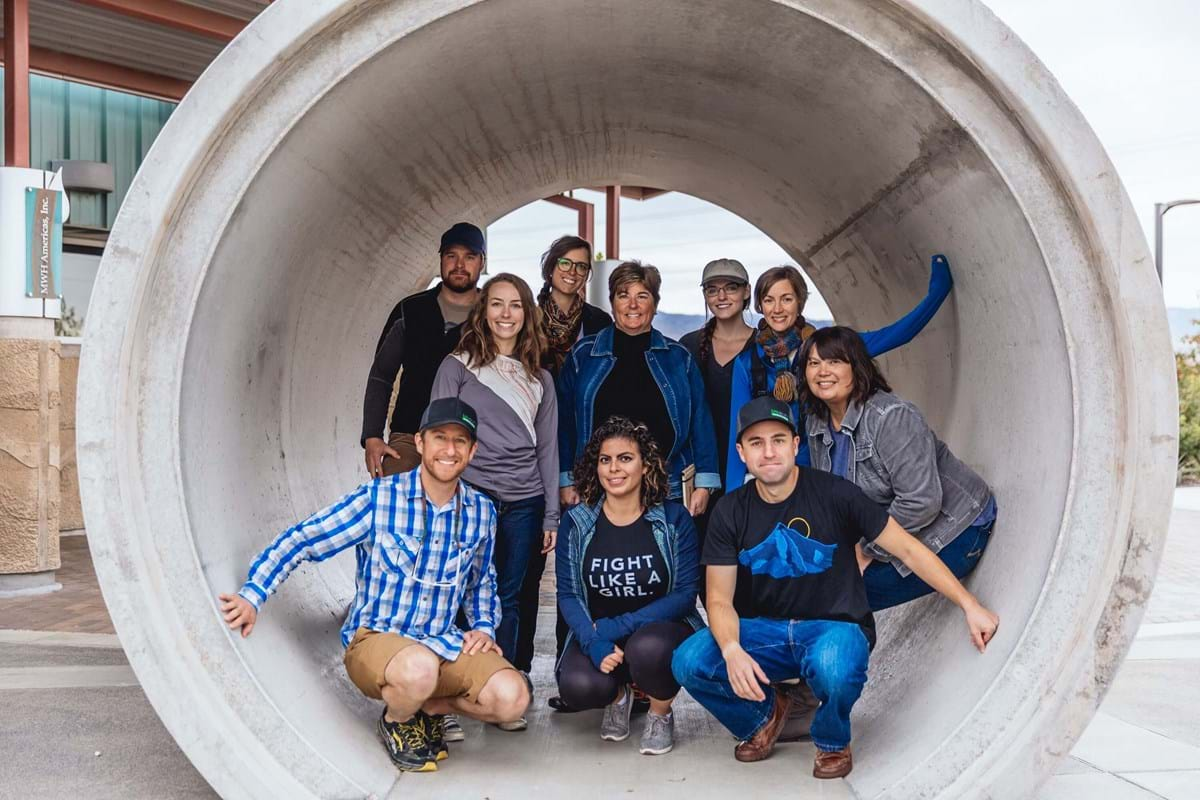 Group of people posing in a large section of pipe