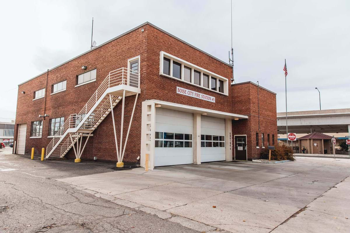 Older brick two story fire house building with two garage bays