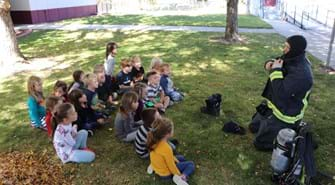Group of about 20 school children sit in grass while Boise Firefighter puts on full suit