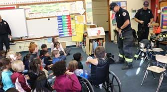 Firefighter stands in front of classroom of school aged children
