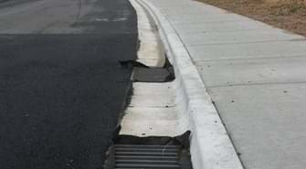 Photo of street with drains next to curb and sidewalk with drop inlets in drains