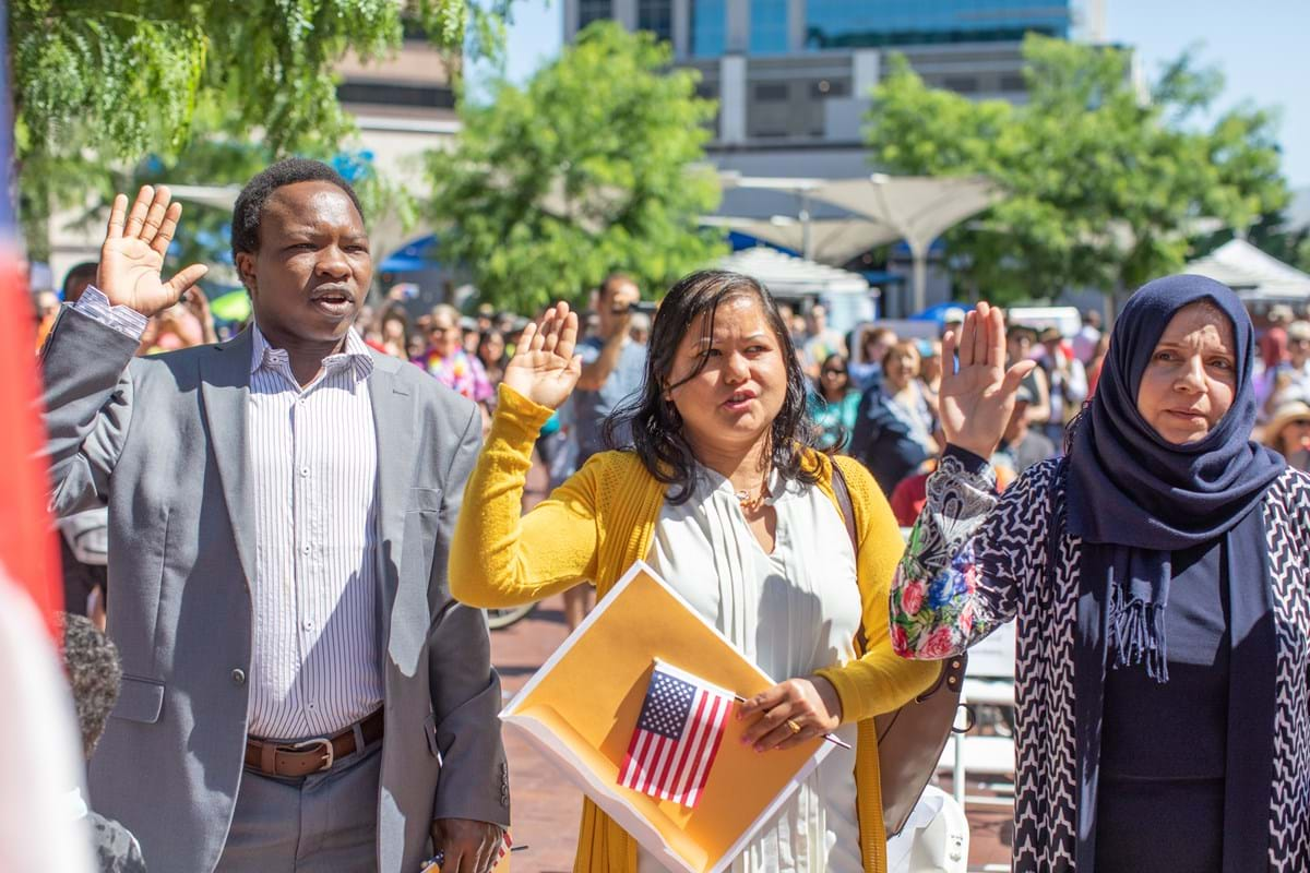 Three people stand outside with their right hands raised, taking the United States oath of citizenship