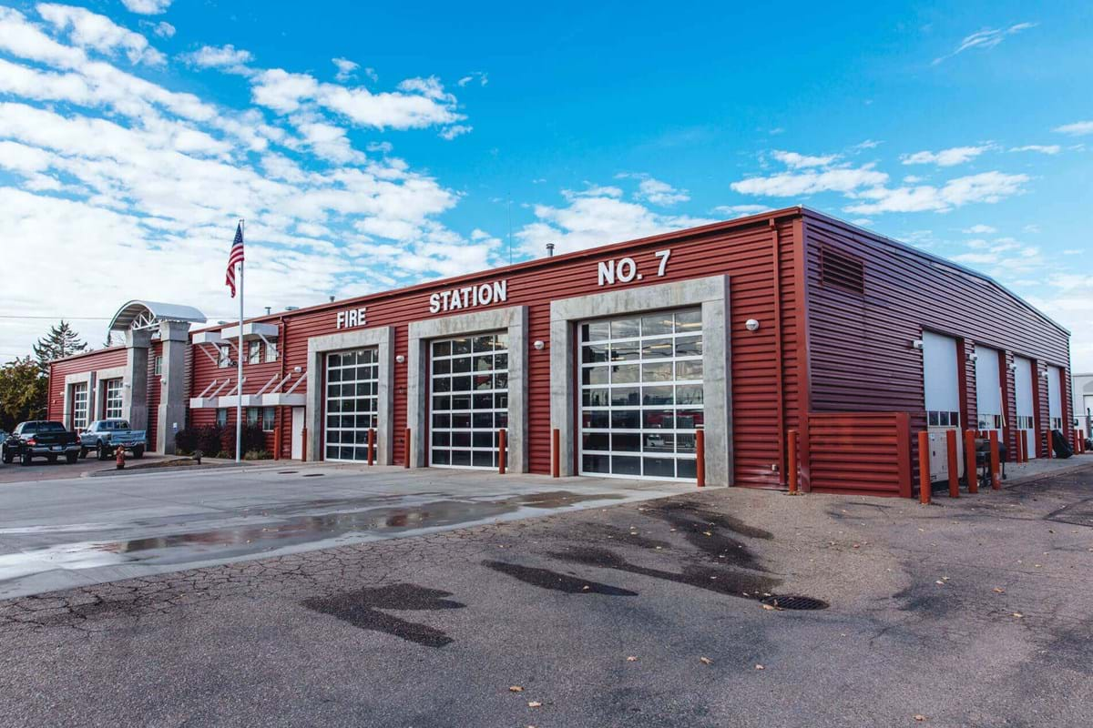 Large fire station building with three garage bays and bright blue sky