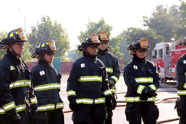 5 firefighters in full gear listen intently as an instructor, out of frame, gives instructions.
