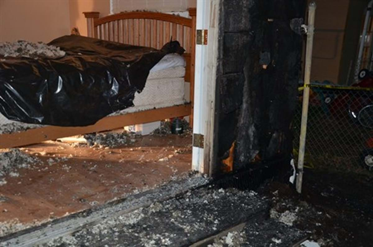 Interior of bedroom and hallway of house with significant fire damage