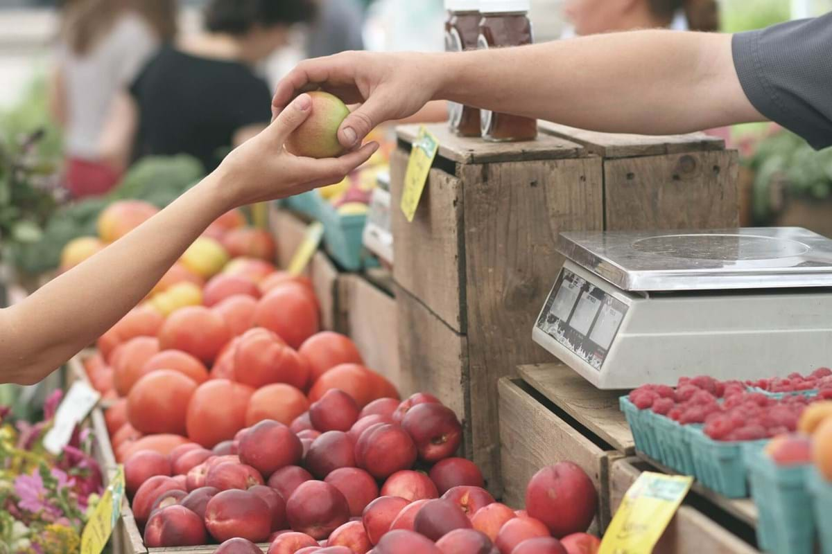 Close up photo of person handing a peach to someone else over a shelf of other fruits at a farmer's market