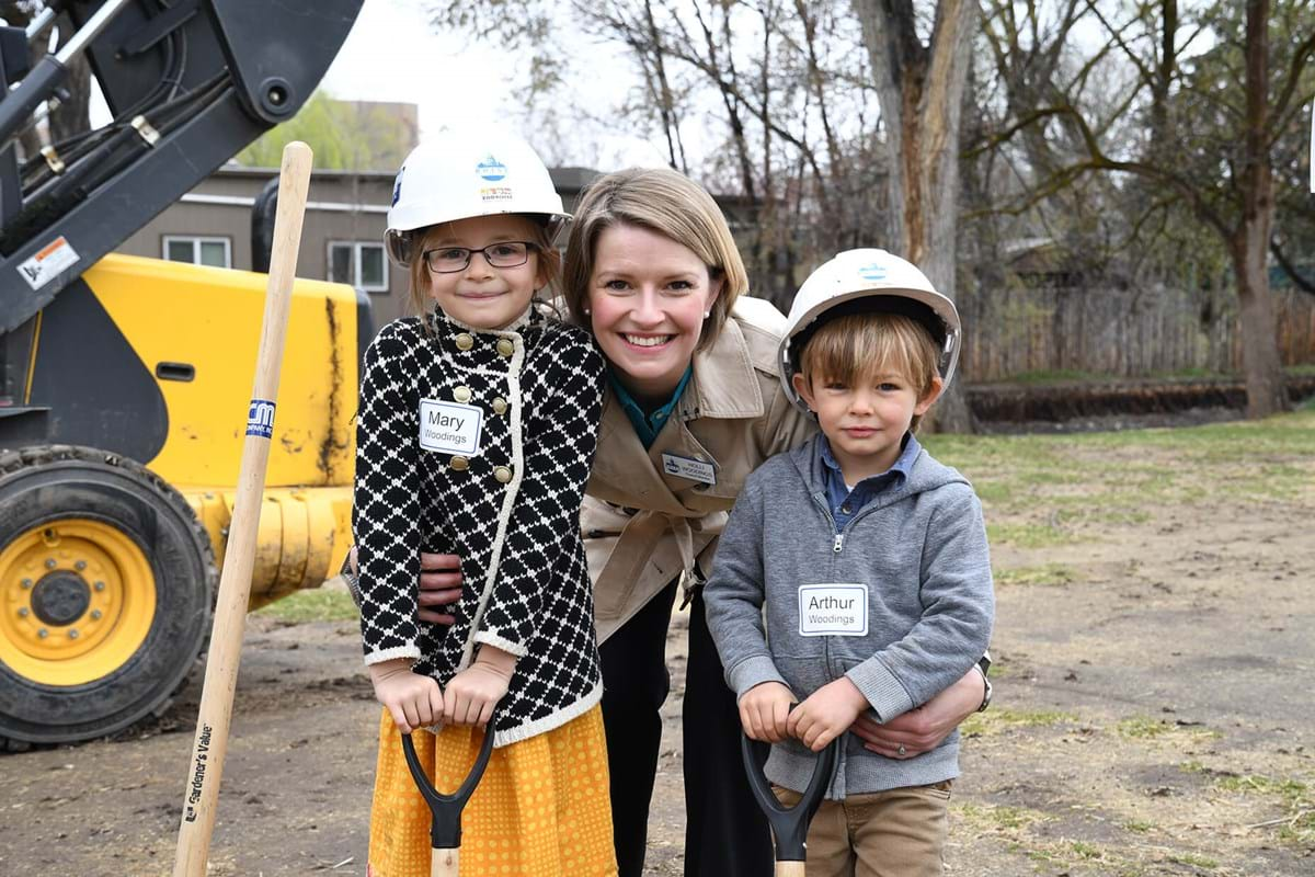 Woman smiling with two children wearing hard hats