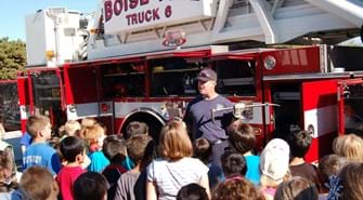 Firefighter holds tools with truck in background and kids crowd around to look