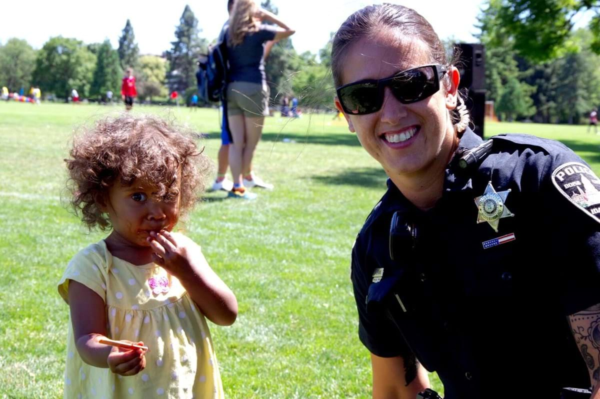 Female officer smiling with child
