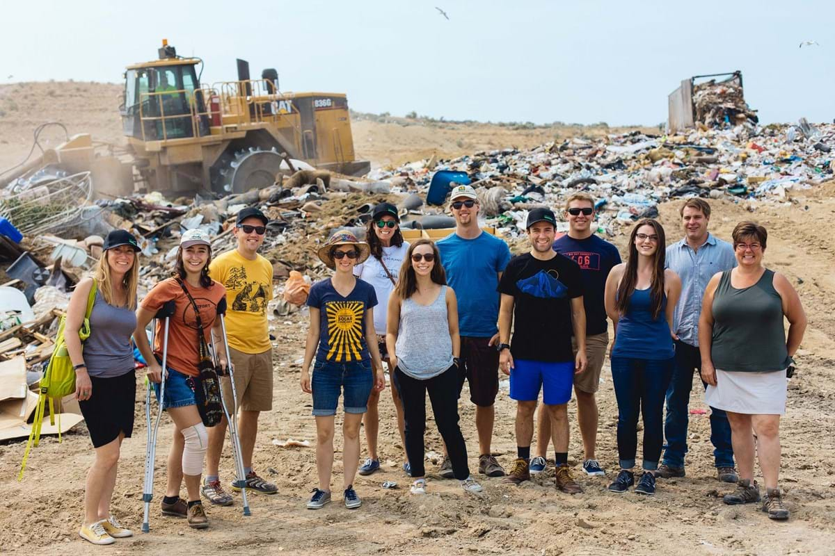 Group of people standing in front of a tractor moving trash