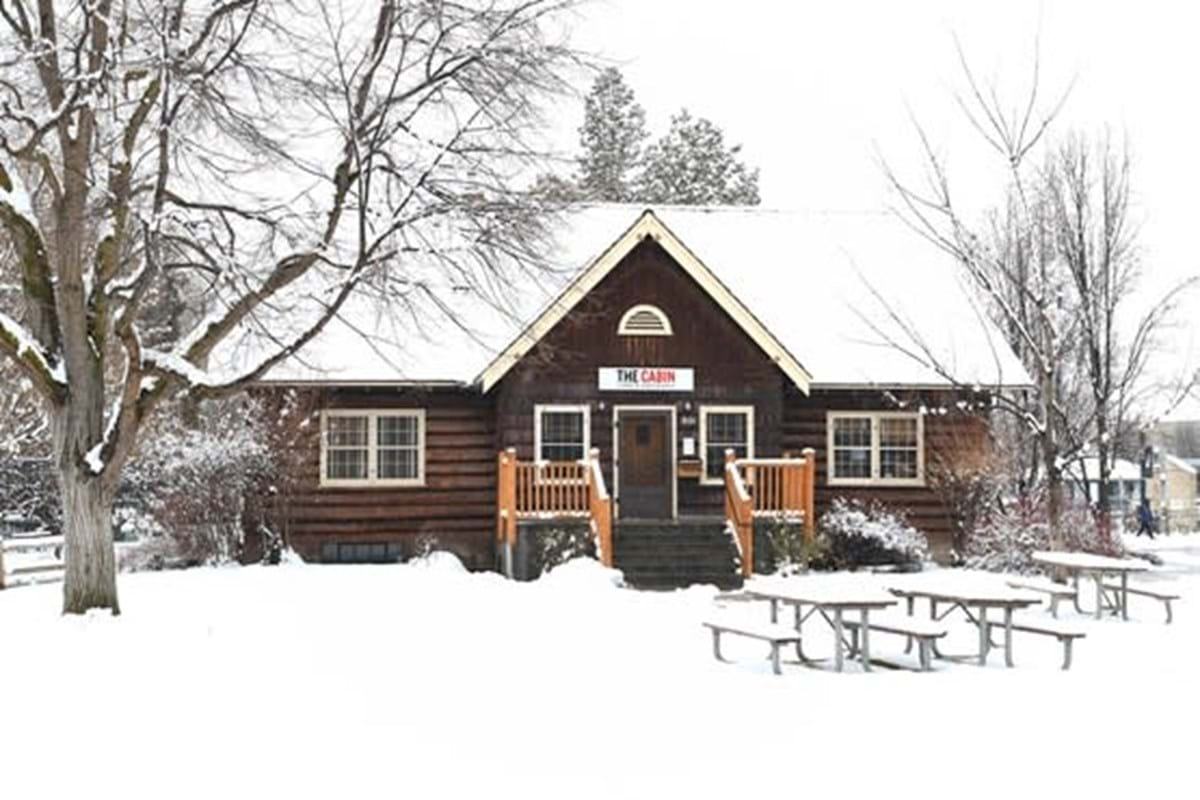 Log cabin in snow with picnic tables in front.