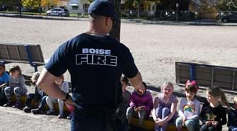Kids sit on a curb with a Boise firefighter in front of them