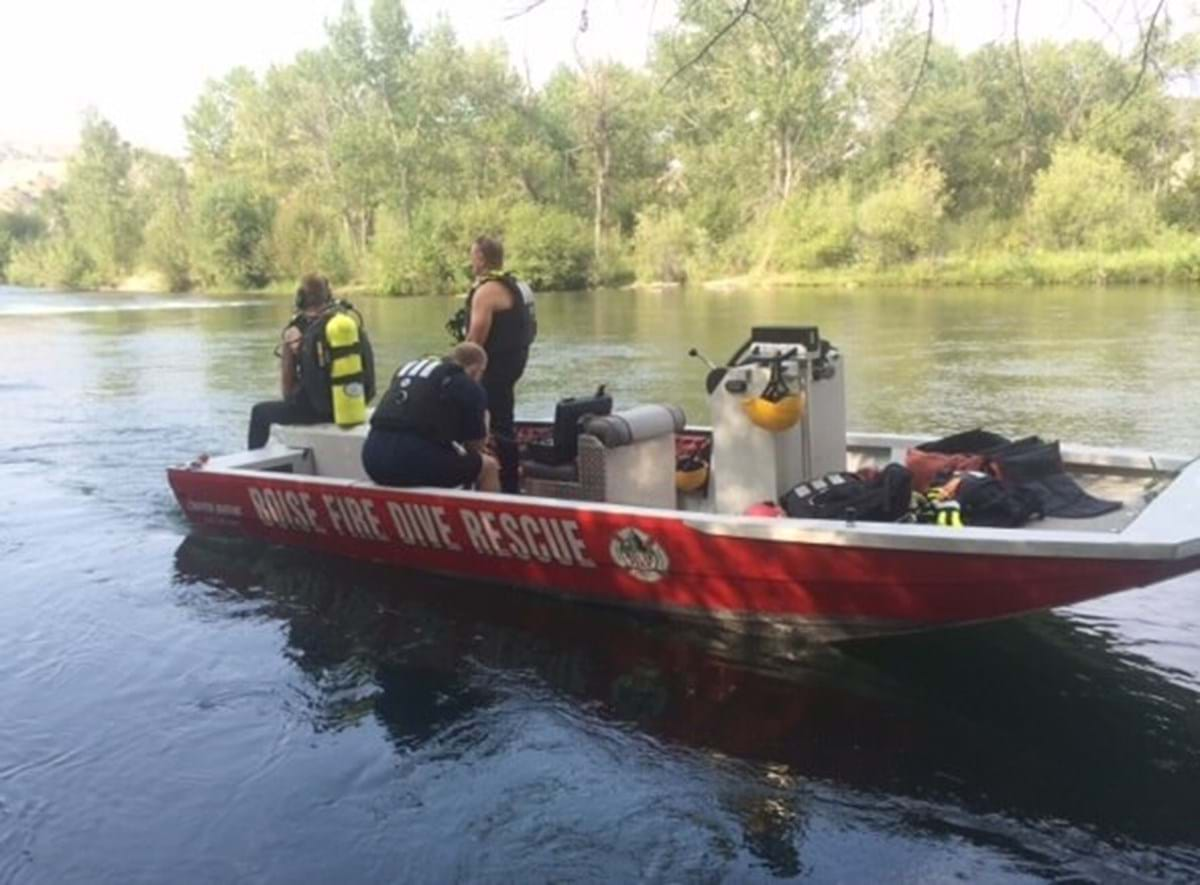 "Boat in river with words ""Boise Fire Dive Rescue"" with three firefighters on board"