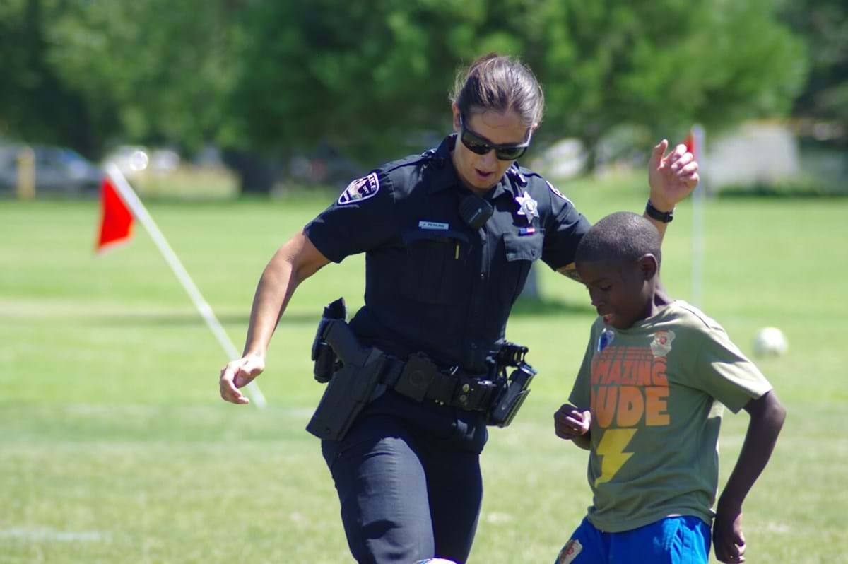 Female officer playing soccer with a child