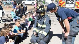 Firefighter in full gear kneels in front of students. Another firefighter looks on.
