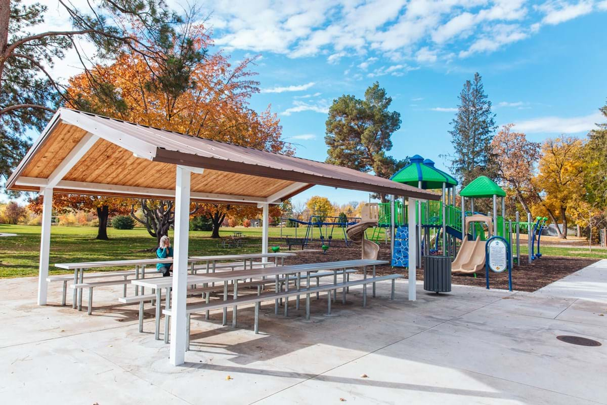Outdoor covered picnic shelter with playground in background
