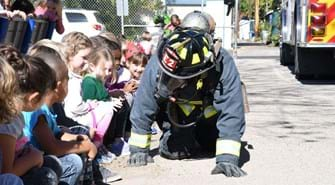 Firefighter crawls on ground in full gear, including mask, so children can see him up close