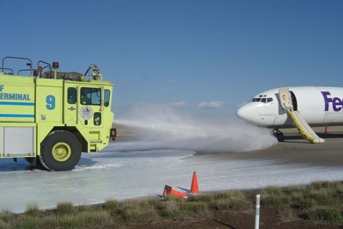 Aircraft rescue fire fighting engine sprays water at an airplane on a runway