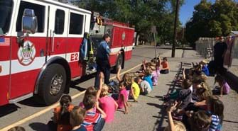 Kids sit on ground in front of fire truck as a firefighter walks in front of them answering question