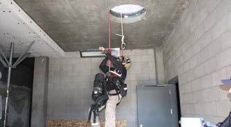Man is harnessed with oxygen tank and coming through hole in ceiling