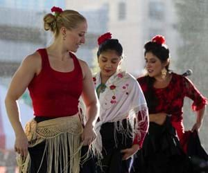 Three women in red, black and white dress are dancing