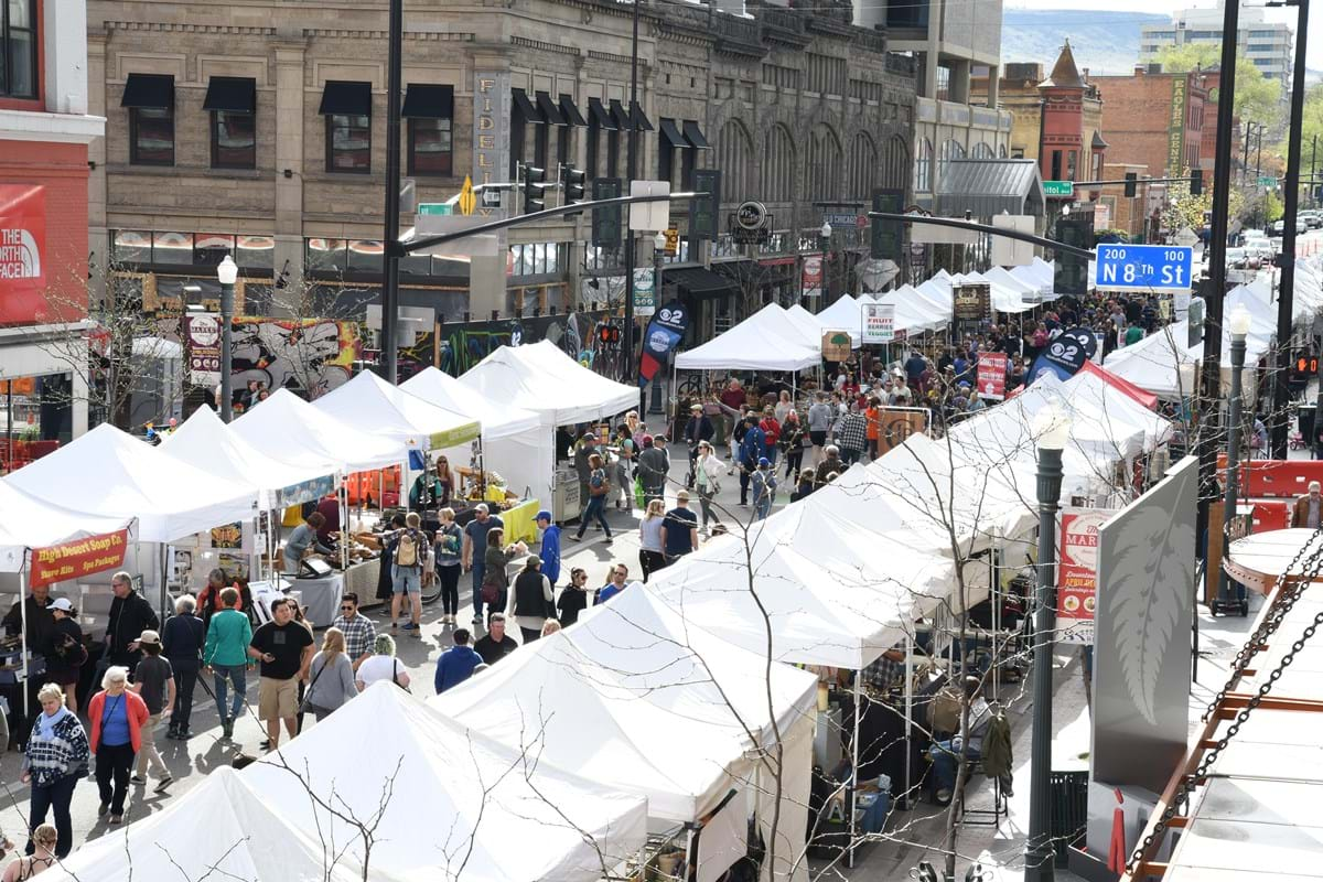 Photo taken from above of downtown street lined with tents for farmers market with people walking around them.