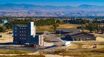 Wide photo of the training facility showing buildings with foothills behind