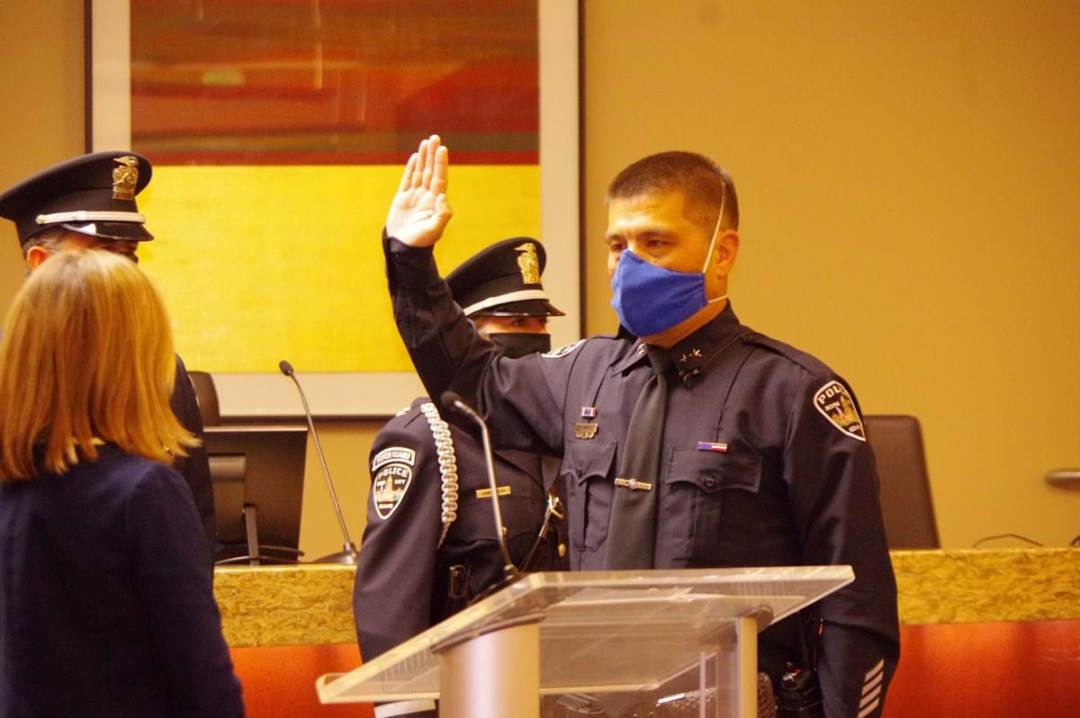 Chief Lee raising hand as he is sworn in by Mayor McLean