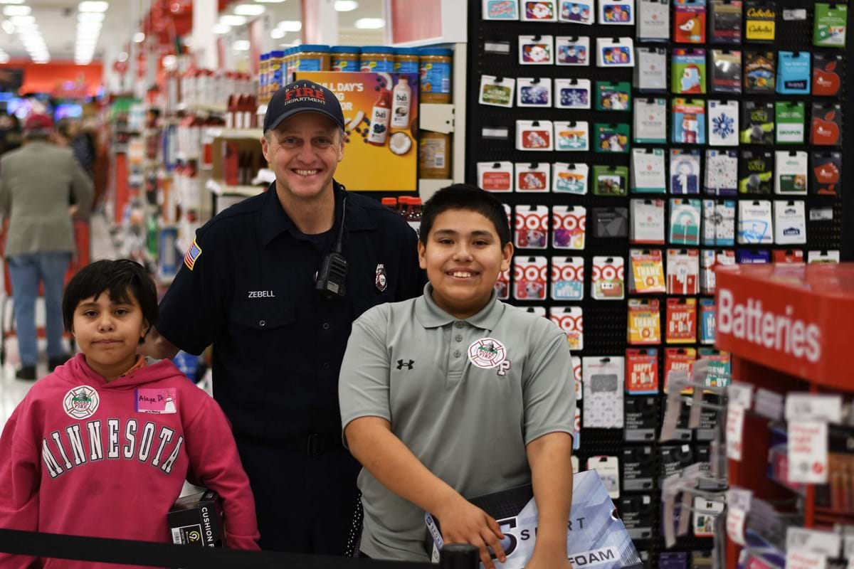 Boise Firefighter helps two children at the annual holiday shopping spree