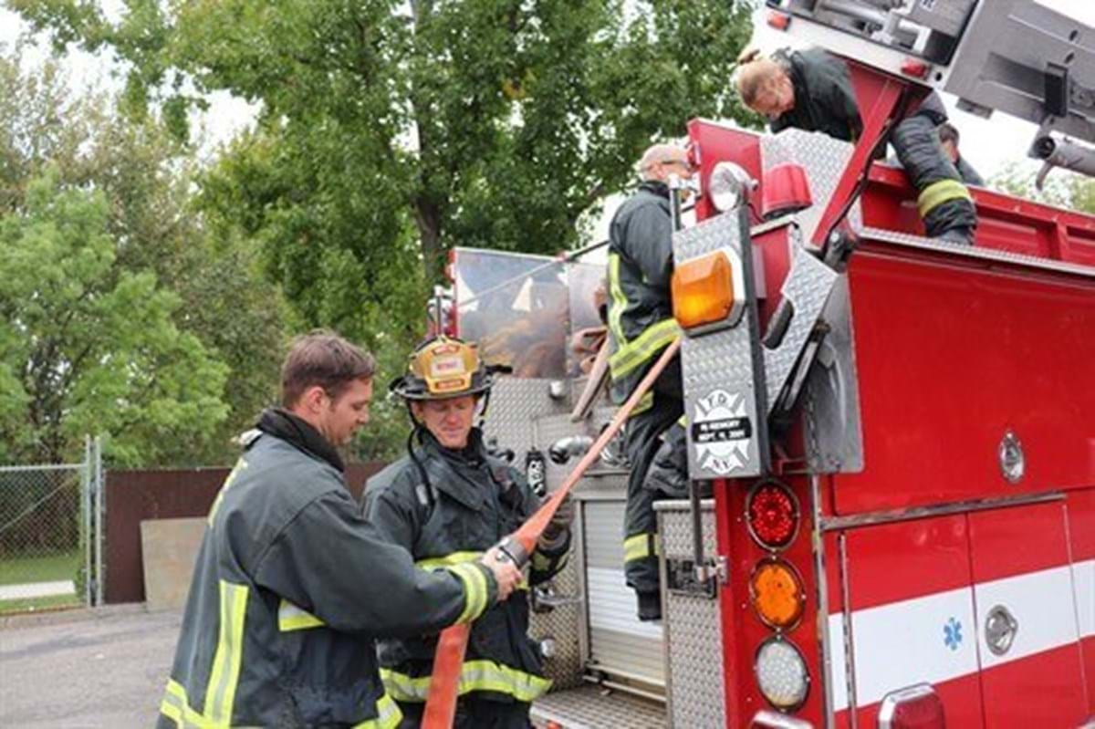 Firefighters take a hose from the back of a truck.