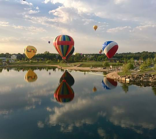 Hot air balloons over pond